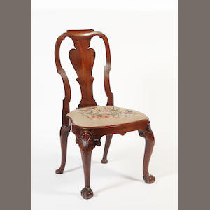 A George I walnut standard chair, with solid vase splat back, drop in needlework seat, on shell carved cabriole legs with claw and ball feet.