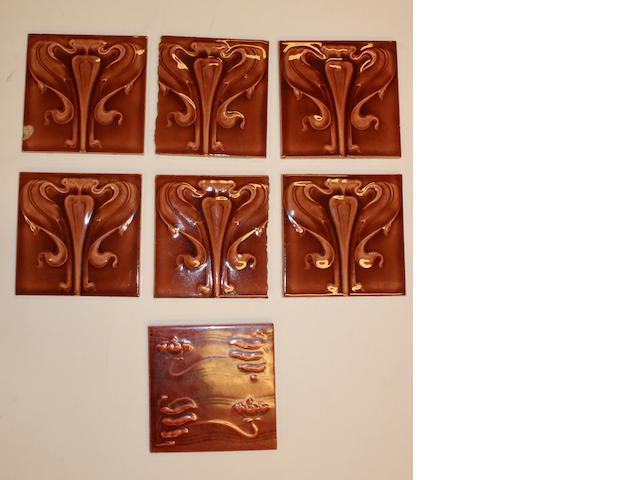 A set of six maroon Art Nouveau tiles and a similar tile