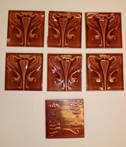 A set of six maroon Art Nouveau tiles and a similar tile