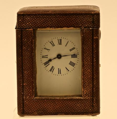 A brass carriage clock with white enamel face, Corniche case and leather carrying case