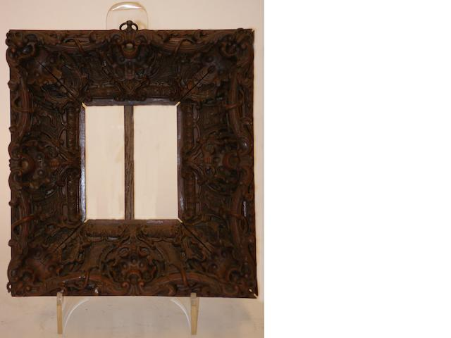 An antique carved wooden picture frame profusely carved in floral scrolls