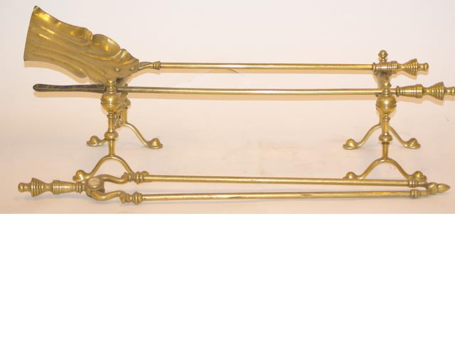 A pair of brass andirons and a set of three fire irons