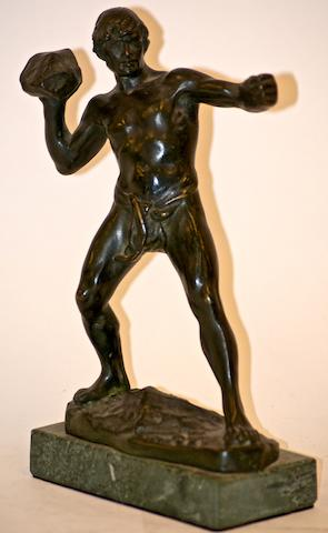 A bronze figure of a man in a loincloth throwing a rock