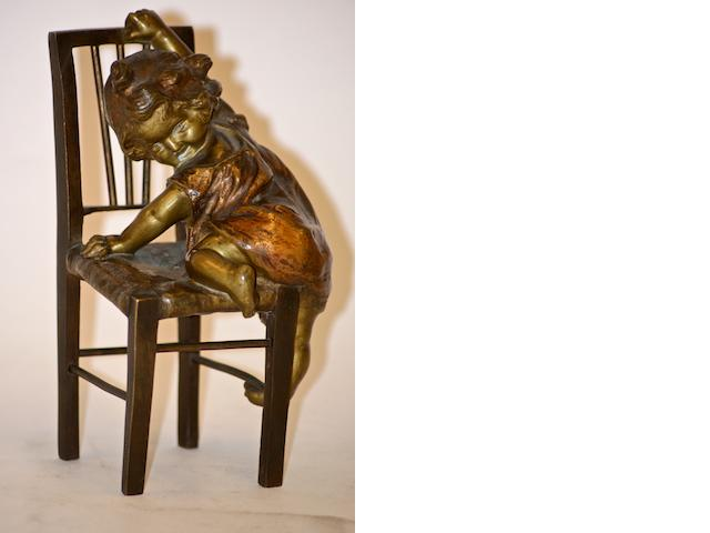 A Bronze figure of a young girl climbing on a chair