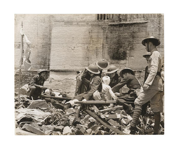 CHINA - CANTON CAPA (ROBERT) Civil defense volunteers attend the injured after a Japanese air raid; volunteers amongst bombed houses