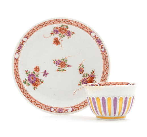 A Meissen teabowl and saucer with moulded reeding, decorated with Böttger lustre, with kakiemon sprigs (restored rim chip to cup)