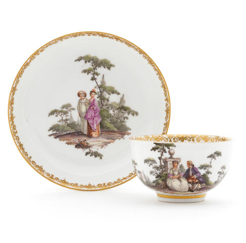 A Meissen teacup and saucer decorated with Watteau scenes