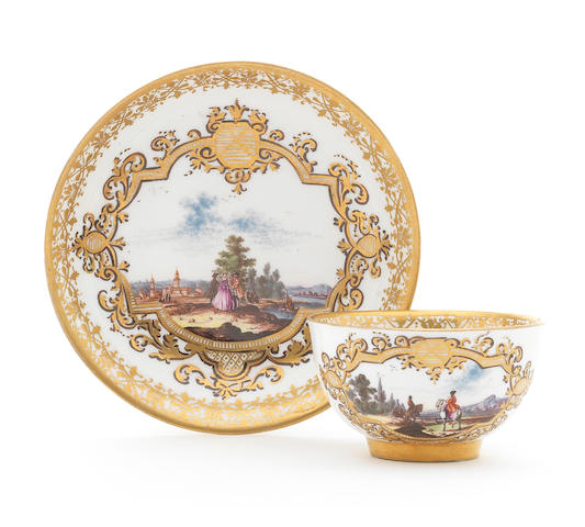 A Meissen teabowl and saucer with European landscape scenes