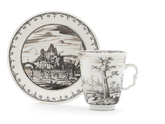 A Du PAquier tall cup and saucer decorated with Schwarzlot landscape scenes in the manner of Preissler