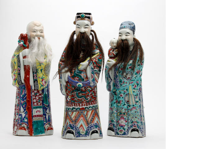 A collection of three Chinese famille rose export porcelain luohan figures  Early 20th Century