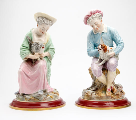 A pair of Royal Worcester figures of a boy and girl with cat and dog