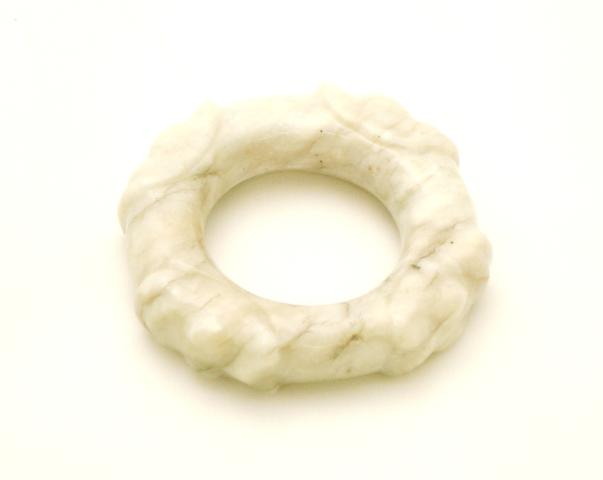 A carved pale grey jade ring