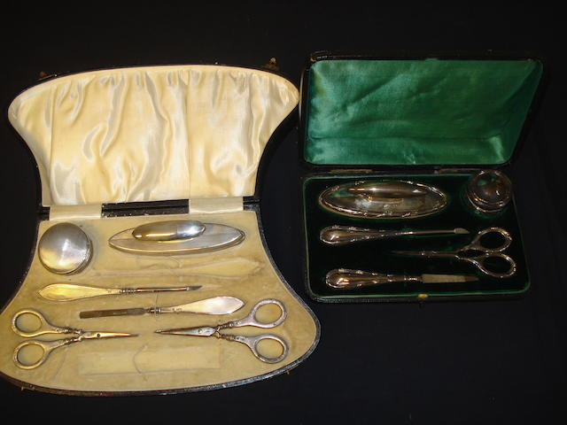 A silver boxed manicure set together with another
