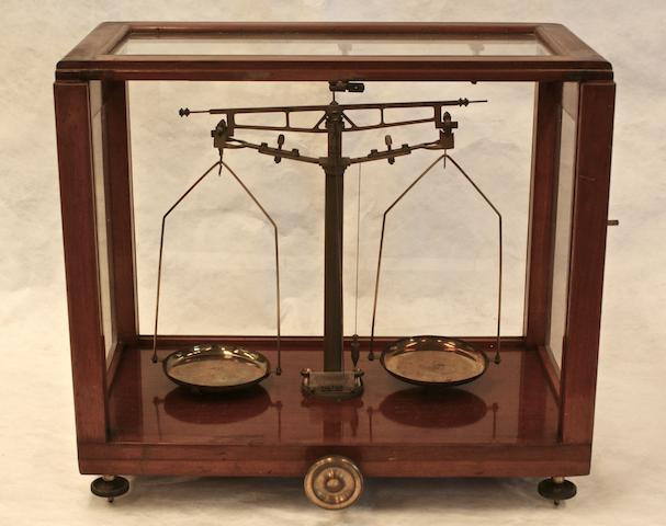 A glazed case set of brass balance scales and weights