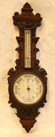 An Edwardian carved oak wall aneroid barometer/thermometer with leaves and scrolls