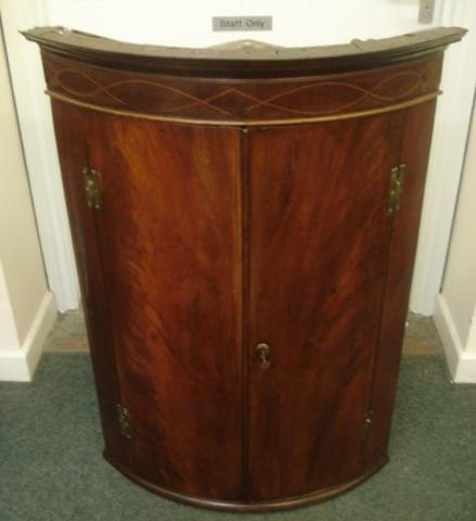 A George III mahogany bowfronted wall hanging corner cabinet, with boxwood strung frieze and enclosed by a pair of elliptical doors, 78cm.