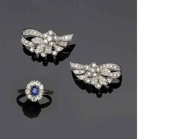 A pair of diamond earrings and a sapphire and diamond cluster ring The earrings modelled as ribbon loop and floral sprays, set throughout with brilliant and baguettte-cut diamonds, to stud fittings, the cluster ring with mixed-cut sapphire surrounded by brilliant-cut diamonds, shank stamped 'platinum'.