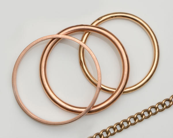 Three 9ct gold slave bangles And a hollow curb-link chain bracelet, to padlock clasp, gross weight 63.5gm.