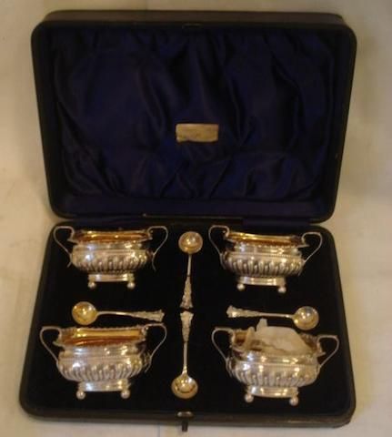 A cased set of four parcel gilt salt cellars, of rectangular half gadrooned form with twin handles on four ball feet and spoons, Birmingham 1896, and a 'lighthouse' silver caster with wrythen body pierced cover and spiral finial, Chester 1905.