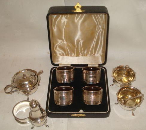 A cased set of four silver on wood napkin rings, engine turned decoration, a pair of panel gilt salts, spoons, mustard pot and spoon and pepperette, Birmingham 1905, 1907 and a plain napkin ring.