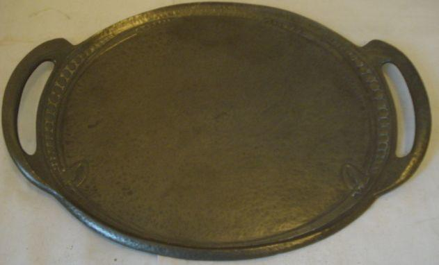 A Liberty & Co, Tudric pewter tea tray, after a design by Archibald Knox, oval, with entralic knot and beadwork, stamped marks and pattern, 0311, 35 x 25cm.