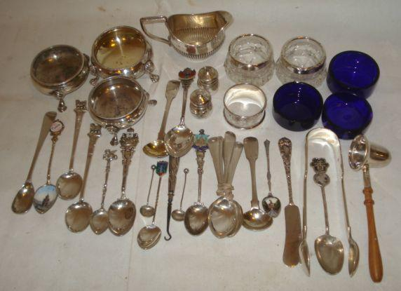 A collection of silver items to include:- a candelabra salt by Hester Bateman, 1777, glass liner, another 1760, by a different makers, a Victorian bright cut salts, 1871, a small half gadrooned milk jug, 1907, miniature two piece cruet, pair of fiddle pattern sugar tongs, 18 various condiment commemorative and teaspoons, some enamelled, a napkin ring, modern candle snuffer silver handled button hook two silver and glass salts and spoons and a butter knife.