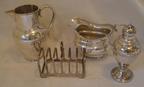 A Victorian silver jug, with high neck and ovoid body with beak spout by Barnards 1882, a cushion shape milk jug with gadrooned rim on four bun feet Birmingham 1915, a pear shaped sugar castor with Celtic band Dublin 1918, and a six division silver toast rack, by Elkington & Co, 1962, 22ozs.