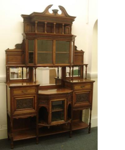 An impressive Victorian walnut chiffonier, of architectural style, foliate carved and panelled, the superstructure with bevelled mirrors, a plush lined cabinet enclosed by a pair of bevelled glazed doors, with a shelf above and to the sides, the base with a sunken centre a glazed cupboard below flanked by drawers and cupboards with an undertier, 168cm wide, 248cm high.