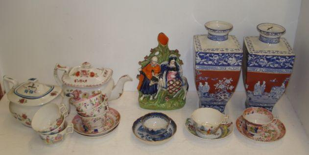 A Victorian Staffordshire figure group, The Flight Into Egypt, a Chinese Export blue Willow pattern tea bowl and saucer, gilt bordered, two early 19th Century English floral painted silver shape teapots and two similar period part tea services, decorated in the Oriental palette, and a pair of square English tapering vases, blue transfer printed and painted in iron red with figures in a fenced garden in the Chinese palette.