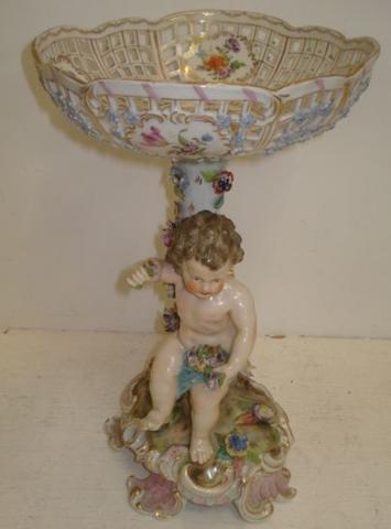 A Dresden style porcelain fruit stand, the pierced circular basket, painted with floral bouquets and swags, supported on a floral encrusted tree stump and a putti with flowers, scrollwork base, 33cm.