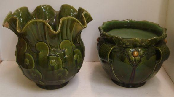 Two Bretby green glazed jardinieres, one with crimped neck and moulded sides, the other with four strapwork side handles interspaced by fruits and leaves, impressed marks, and a Victorian green glazed jardiniere stand, moulded with winged animal masks, leaf scrolls and claw feet, concave sided platform base and brown glazed top, 50.5cm high. (3)