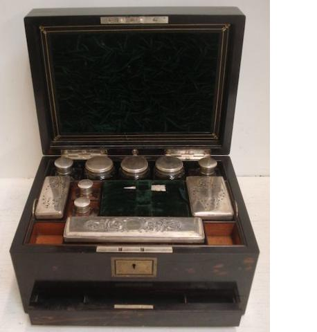 A Victorian coromandelwood dressing case, labelled 'Parkins & Gotto, 24 & 25 Oxford St, London', the hinged cover fitted with a pocket and a lift-out mirror and enclosing a green velvet and satin lined interior fitted with electroplate mounted glass boxes, bottles and jars, a lift-out tray, a catch releases a 'secret' drawer fitted for jewellery, initialled in a cartouche,31cm.