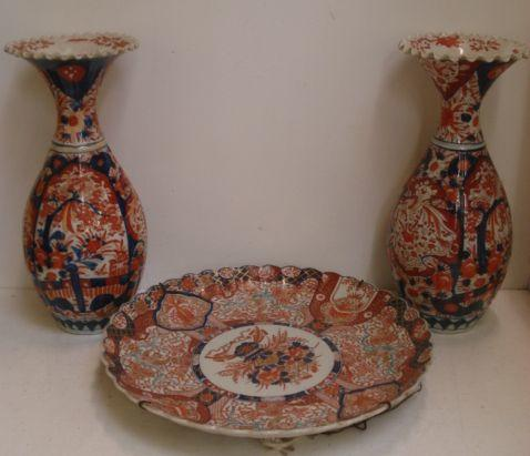 A large Japanese Hizen Imari dish, painted with a central jardiniere of flowers in a circular cartouche, enclosed by a border of segmented panels of birds amongst foliate, 46cm, and a pair of similar period club shape vases, 45cm. (3)