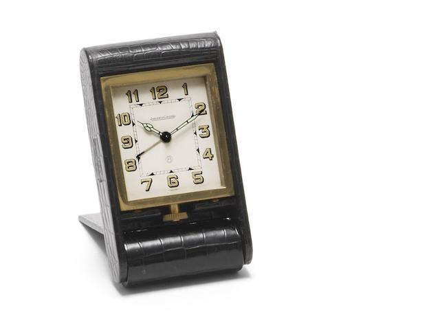 Jaeger-LeCoultre. A gilt metal and alligator 8-day manual wind travel alarm clock with papers Ref:AD0524076, Case No.131137, Sold 3rd December 1971 in Geneva
