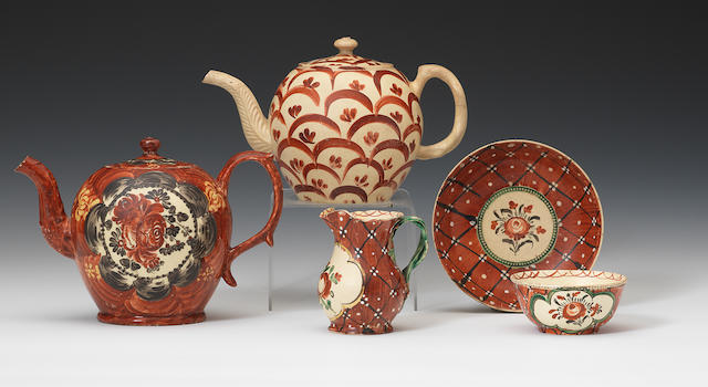 Two teapots and covers, a teabowl and saucer and a creamjug, all red scale patterns
