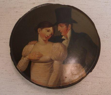 A Stobwasser style circular papier mache snuff box, earl 19th Century, the pull-off cover painted with a young lady and gentleman, 9.5cm.