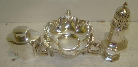 A George V lobed circular silver bon bon dish,  Mappin & Webb, Birmingham 1910, with three scrolled side handles, an Edwardian shaped oval silver tea caddy, Harry Wright Atkin, Sheffield 1906, with pull-off cover, and a George I style octagonal castor, Goldsmiths & Silversmiths Company, 1910, 11ozs. (3)