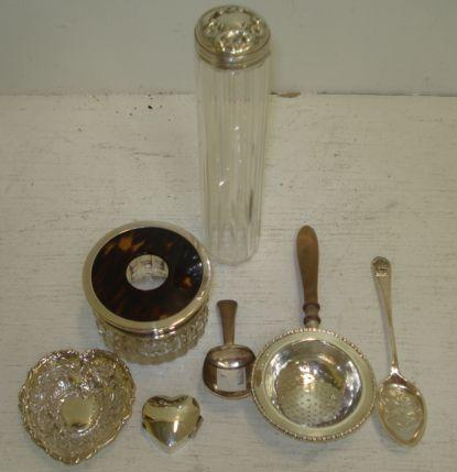 A George III silver caddy spoon, Joseph Taylor, Birmingham 1809, with shovel bowl, and the following silver, a tea strainer, Birmingham 1932, with turned wooden handle, embossed heart shape bon bon dish heat shape pill box, mounted cut glass and tortoiseshell hair tidy, mounted glass toilet jar and a Commemorative spoon. (7)