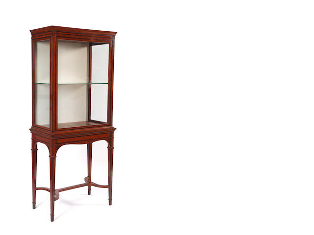 A George III style satinwood mahogany boxwood and ebony strung vitrine, late 19th Century, the moulded cornice above a glazed door and glazed sides enclosing a plate glass shelf, the projecting base with an undulating apron, on square tapered legs united by curved stretchers, 80cm.
