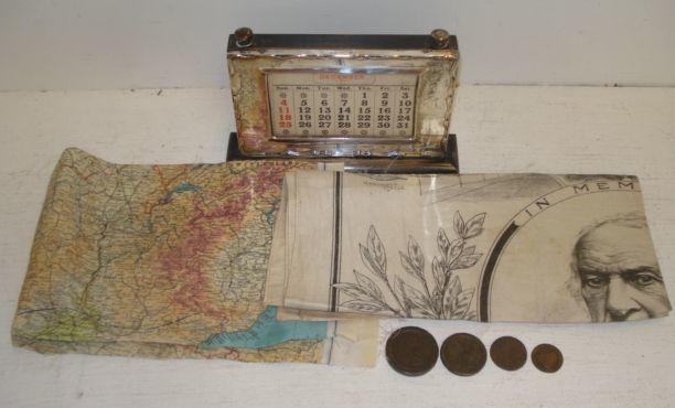 A silver mounted perpetual calendar, Birmingham 1926, a printed cloth in memoriam for William Ewart Gladstone, a silk zones of France World War Two map, a Spalding half penny token, cartwheel penny 1797 and two others.