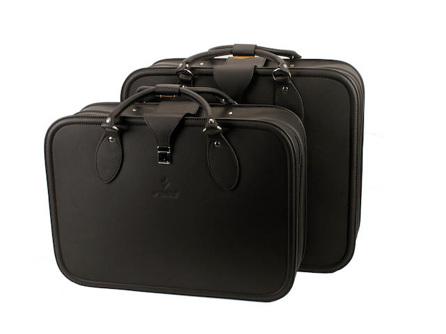 Two Ferarri black leather suitcases and one black leather suit bag