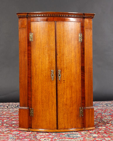A George III mahogany crossbanded oak bow front corner cupboard