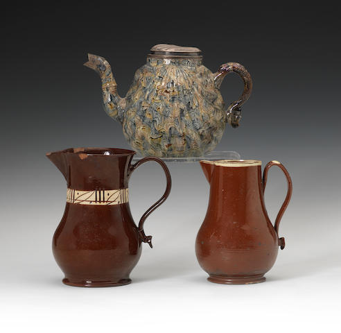 A Staffordshire solid agate pecten shell teapot and replacement cover and two glazed red cider jugs, circa 1750