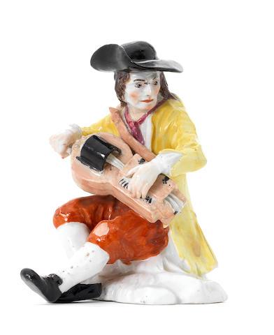 A Meissen beggar playing the hurdy-gurdy, 18thC,