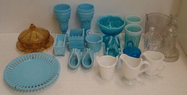 A large collection of Sowerby and other pressed blue, white and clear glasswares, including pairs of vases, posy baskets, flower holders, cream jugs, dishes and plates, and a similar amber glass butter dish and cover. (56 pieces)