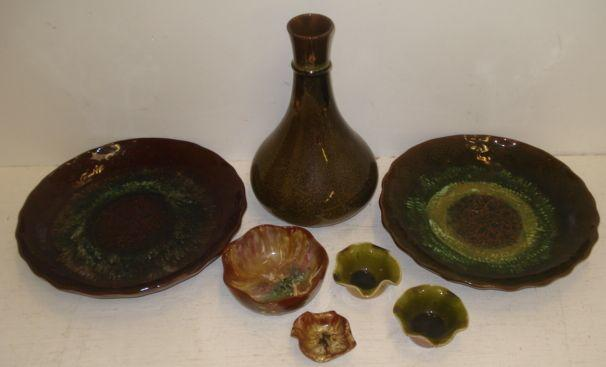 Christopher Dresser for Linthorpe, a bottle vase with a moulded rim in a brown and ochre streaked and speckled glaze, 24cm, also two crimped edge shallow dishes, the centres with moulded flowers and foliate in streaked glazes, all with impressed marks and signatures, 25cm, and four crimped edge scrolls, variously decorated in Monochrome and streaked glazes, one painted with leather. (7)