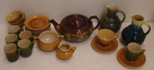 A Linthorpe part tea service, comprising four tea cups, four saucers, milk jug, sugar basin, all in a pooled ochre glaze, impressed marks and numbered, also six coffee cups with angular handles and saucers, in a pooled olive glaze, two stepped bulbous jugs in streaked glazes, pattern no. 858 and a compressed circular silver shape teapot. (25)