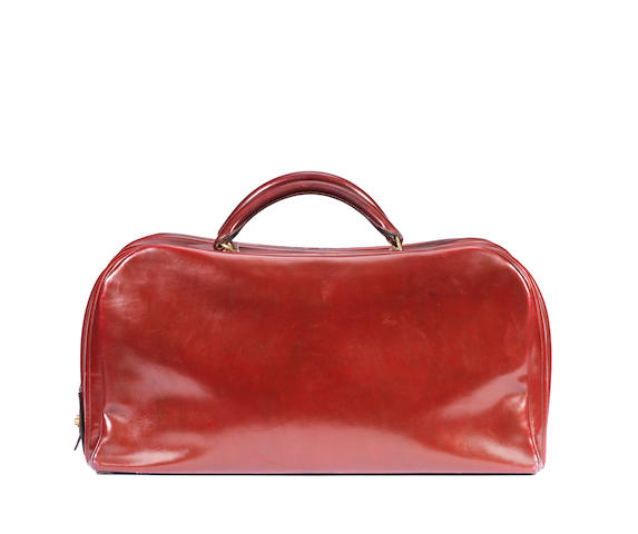 An Hermes red leather suitcase