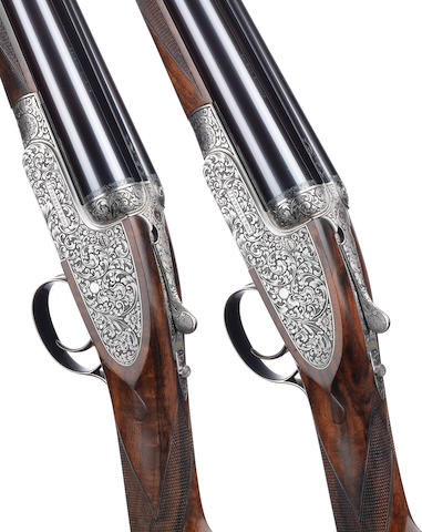 A fine pair of M. Smith-engraved 12-bore (2¾in) single-trigger self-opening sidelock ejector guns by J. Purdey & Sons, no. 30371/2 In their leather motor-case with canvas cover and makers accessories