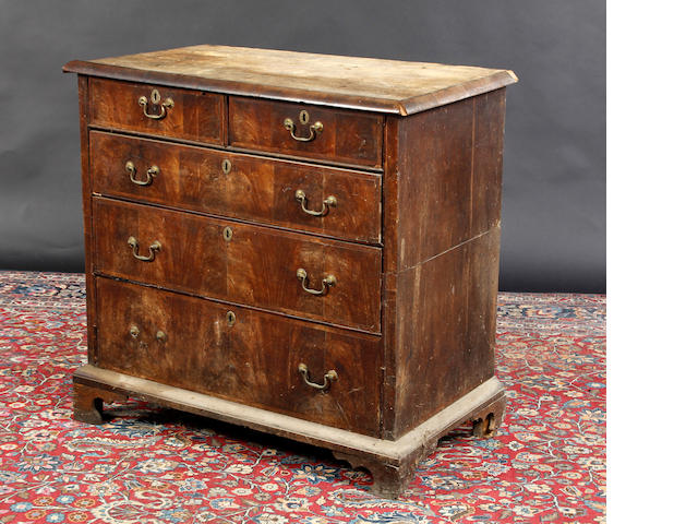 A walnut chest of drawers In need of restoration